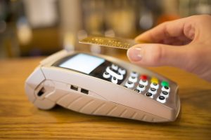 Woman paying with NFC technology on credit card, restaurant, shop